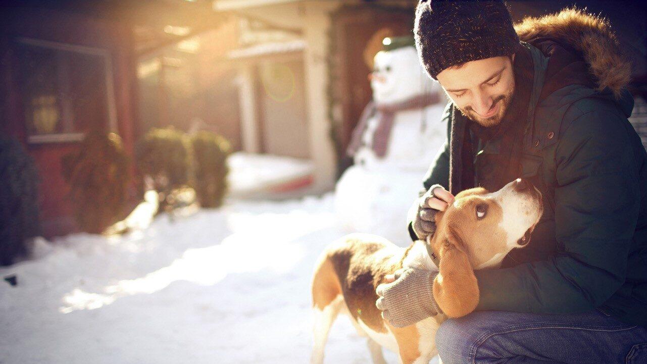 man met hond in de sneeuw